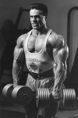 Bodybuilder John Terilli doing dumbbell lifts using heavy weights